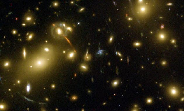 L'ammasso Abell 2218, nella costellazione del Drago. Oltre alle galassie che lo compongono, si notano diversi deboli archi (per la cronaca, sono 120): sono le immagini ingrandite e distorte di galassie più lontane (vedi lo schema più in basso, in questa pagina).|NASA/ESA