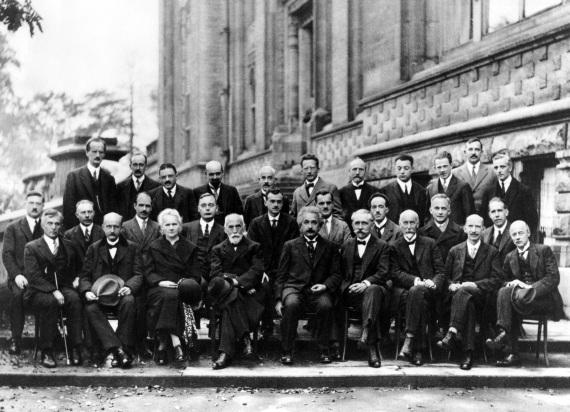 29 persone (una sola donna, Marie Curie), 17 erano o sarebbero diventati premi Nobel, per la fisica o la chimica. Sono i partecipanti alla V Conferenza Solvay, dedicata ufficialmente a elettroni e protoni, ma che in realtà ospitò il primo grande dibattito sulla fisica quantistica, mettendo a confronto i sostenitori dell'interpretazione della meccanica quantistica secondo la scuola di Copenhagen e un nutrito gruppo di scettici che non credeva nella sua natura intrinsecamente probabilistica. I primi avevano come leader indiscusso Bohr e i secondi erano rappresentati da Einstein. I due scienziati si contrapposero a colpi di esperimenti mentali (Gedankenexperimente). Sono entrate nella leggenda le animate discussioni che iniziavano già durante la colazione del mattino, quando Einstein proponeva un esperimento mentale all'attenzione di Bohr, il quale poi passava la giornata a trovare una spiegazione che rientrasse nei canoni della meccanica quantistica.