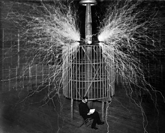 """Spettacolari scariche elettriche scaturiscono da una struttura a bobina, generate da tensioni superiori ai 12 milioni di volt. Così nel 1899 Nikola Tesla sperimentava se la corrente elettrica potesse essere trasportata senza fili, attraverso l'atmosfera, come le onde radio. Ma il """"mago dell'elettricità"""" era anche uno showman: sembra seduto tra le scariche mortali, ma è un trucco fotografico."""