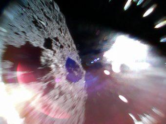 Foto a colori scattata dal Rover-1A alle 4:44 ora italiana di sabato 22 settembre mentre saltava sulla superficie di Ryugu. La metà a sinistra dell'immagine raffigura la superficie dell'asteroide. La chiazza bianca a destra è dovuta alla luce del sole. Crediti: Jaxa