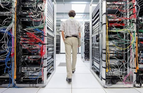 Technician walking through server room of data center © Juice Images / AGF