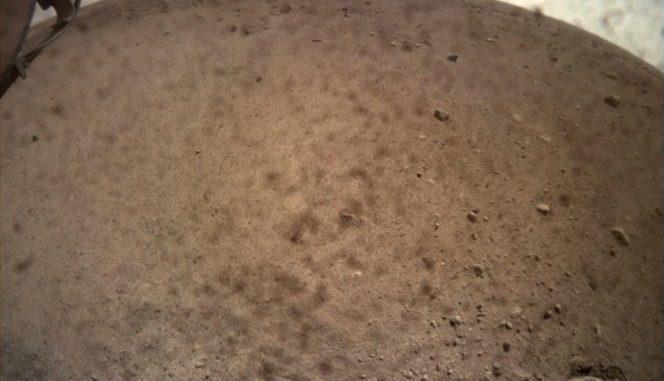 Il lander InSight della Nasa ha attivato la sua Instrument Context Camera (Icc) lo scorso 30 novembre catturando questa vista polverosa di Marte. La fotocamera Icc è dotato di un obiettivo fisheye che crea un orizzonte curvo. Alcuni grumi di polvere sono ancora visibili sull'obiettivo della fotocamera. Crediti: Nasa/Jpl-Caltech
