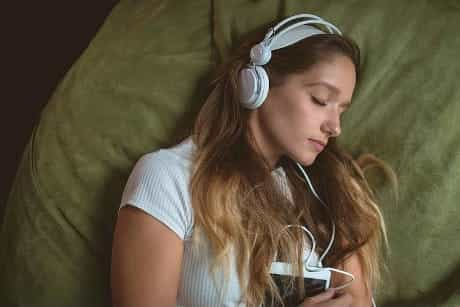 Woman listening music on headphones while sleeping