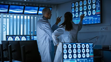 Two Medical Scientists / Neurologists, Talking and Working on a Personal Computer in Modern Laboratory. Research Scientists Making New Discoveries in the fields of Neurophysiology, Science, Neuropharmacology. Understanding Human Brain.