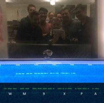 Selfie allo specchio dei membri del team LightSail 2 davanti alla stringa in codice Morse ricevuta dal microsatellite e che conferma il suo stato di salute. Crediti: Dave Spencer / The Planetary Society