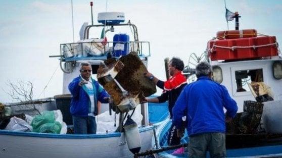 Pescatori che tirano su plastica dal mare
