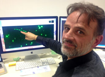 Eros Vanzella, ricercatore all'Inaf di Bologna, indica una delle immagini – ingrandite e replicate dalla lente gravitazionale – dell'ammasso stellare analizzato nello studio da lui guidato. Fra quelli confermati, è a oggi l'ammasso stellare più distante. Crediti: M. Malaspina/Media Inaf