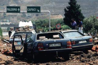 23 maggio 1992: allo svincolo di Capaci, sull'autostrada da Punta Raisi a Palermo, 500 kg di tritolo uccidono Giovanni Falcone, la moglie e 3 agenti della sua scorta. Sono le 17:58: un boato terribile, un intero lembo di autostrada che si solleva, una nube nera altissima, il muro di asfalto e cemento - l'esplosione è tale che viene registrata dai sismografi dell'Istituto nazionale di geofisica. |