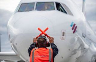 25 September 2020, Hamburg: An Airbus 319 belonging to the airline Eurowings is being briefed by an airport employee on the new apron at Hamburg Airport. After a total construction period of 4 years, the apron was opened on 25 September. Photo: Axel Heimken/dpa (Photo by Axel Heimken/picture alliance via Getty Images)