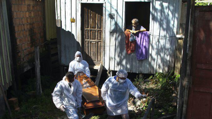 Una persona osserva dalla finestra alcuni lavoratori del servizio funerario pubblico mentre portano via una bara, a Manaus, nello stato di Amazonas, in Brasile, lo scorso 22 gennaio (AP Photo/Edmar Barros, File, LaPresse)