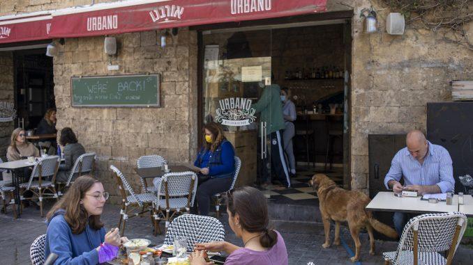 Un ristorante riaperto in seguito all'alleggerimento delle restrizioni contro la pandemia in Israele, deciso in parte in seguito al successo della campagna vaccinale nel paese. (AP Photo/Ariel Schalit)