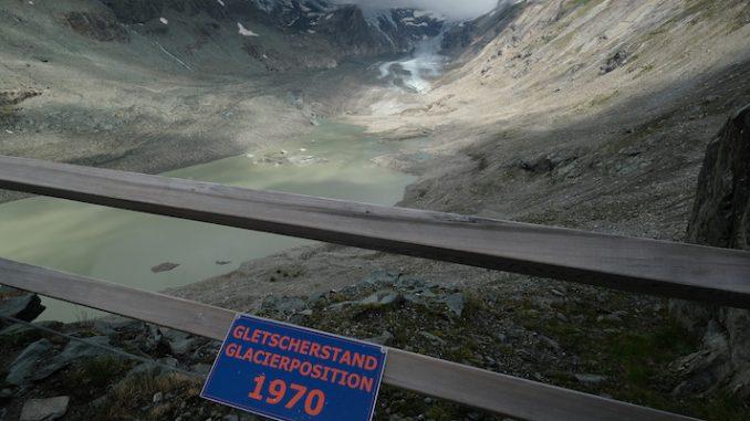 Un cartello indica dove arrivava il ghiacciaio austriaco Pasterze nel 1970, mentre sullo sfondo si vede il ghiacciaio com'era nell'agosto del 2019 (Sean Gallup/Getty Images)